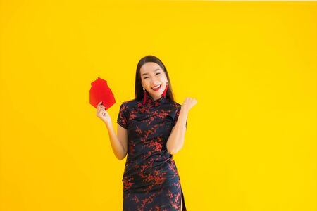 Portrait beautiful young asian woman wear chinese dress with Ang Pao or red letter with cash for chinese new year concept on yellow isolated background
