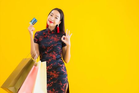 Portrait beautiful young asian woman wear chinese dress with shopping bag , smart mobile phone , credit card for chinese new year on yellow isolated background