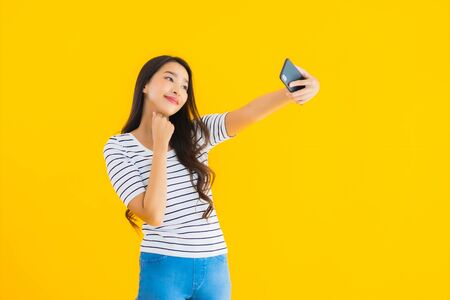 Portrait beautiful young asian woman smile happy use smart mobile phone on yellow isolated background