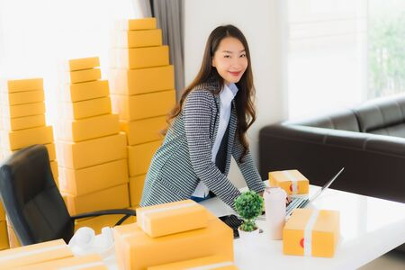 Portrait beautiful young asian business woman work from home with laptop mobile phone with cardboard box ready for shipping online shopping