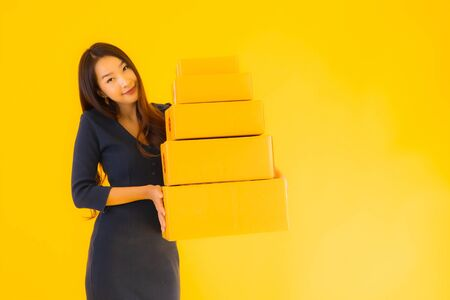 Portrait beautiful young asian woman with cardboard box packkage ready for shipping on yellow isolated background Foto de archivo