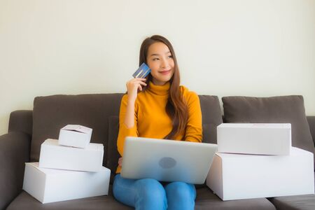 Portrait young asian woman using laptop computer for work with parcel box on sofa in living room interior 版權商用圖片