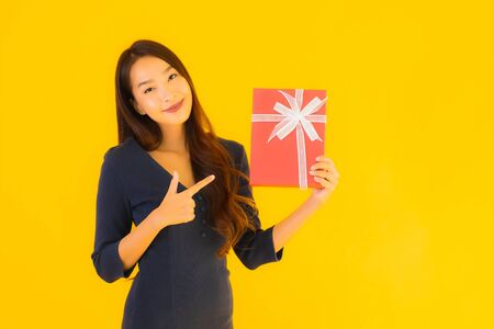 Portrait beautiful young asian woman with giftbox on yellow isolated background Foto de archivo