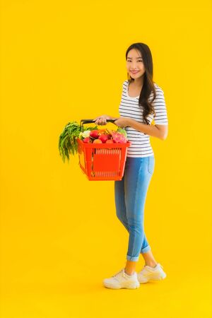 Portrait beautiful young asian woman with grocery basket cart from supermarket in shopping mall on yellow isolated background