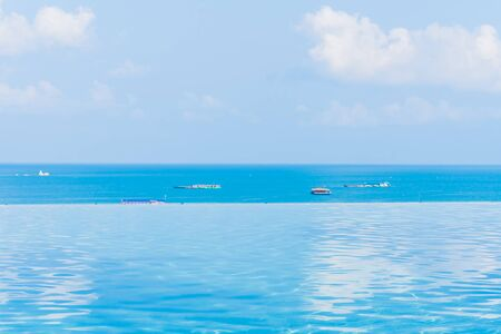 Beautiful infinity outdoor swimming pool with sea ocean view around white cloud blue sky for leisure vacation Stok Fotoğraf
