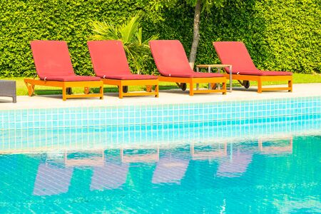 Beautiful empty chair around outdoor swimming pool in hotel resort for travel vacation Stok Fotoğraf