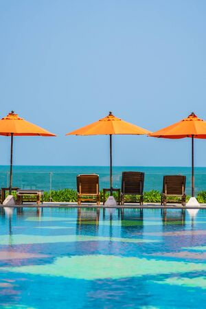 Umbrella and chair around outdoor swimming pool neary sea in hotel resort for holiday vacation