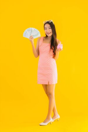 Portrait beautiful young asian woman show a lot of cash or money with piggy bank on yellow isolated background