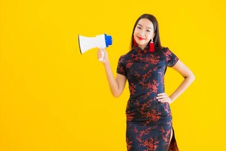 Portrait beautiful young asian woman wear chinese dress with megaphone on yellow isolated background 版權商用圖片