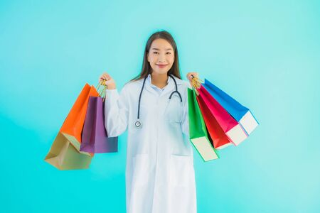 Portrait beautiful young asian doctor woman with colorful shopping bag from shopping mall on blue isolated background