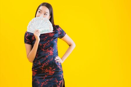 Portrait beautiful young asian woman wear chinese dress with a lot of cash or money for chinese new year concept on yellow isolated background