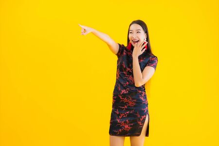 Portrait beautiful young asian woman wear chinese dress with action for chinese new year concept on yellow isolated background