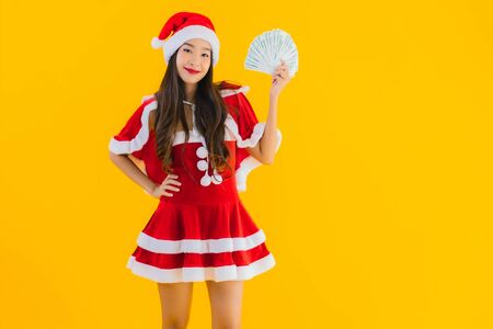 Portrait beautiful young asian woman wear christmas clothes and hat with cash and money on yellow isolated background
