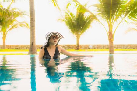 Portrait beautiful young asian woman relax around outdoor swimming pool in hotel resort with palm tree at sunset or sunrise for leisure vacation