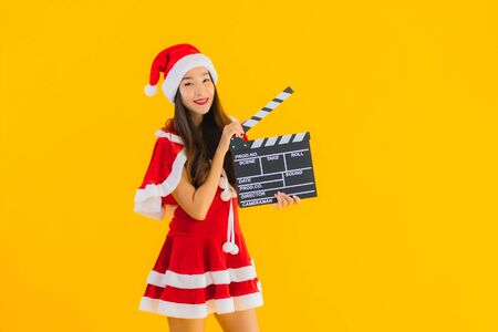 Portrait beautiful young asian woman wear christmas clothes and hat show movie scene cutter plate on yellow isolated background Stock Photo