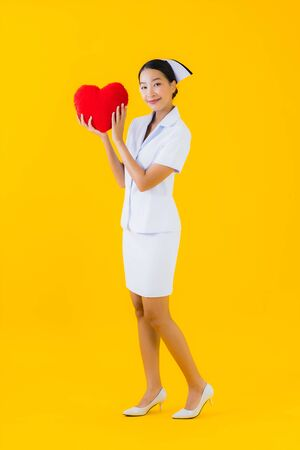 Portrait beautiful young asian woman thai nurse show heart pillow shape and work at clinic or hospital on yellow isolated background 免版税图像 - 150257294