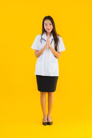 Portrait beautiful young asian doctor woman smile happy work in hospital and clinic on yellow isolated background 免版税图像 - 150257300