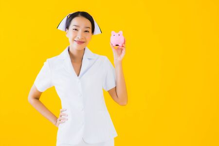 Portrait beautiful young asian woman thai nurse with a lot of cash and money and pink piggy bank on yellow isolated background 免版税图像 - 150257498