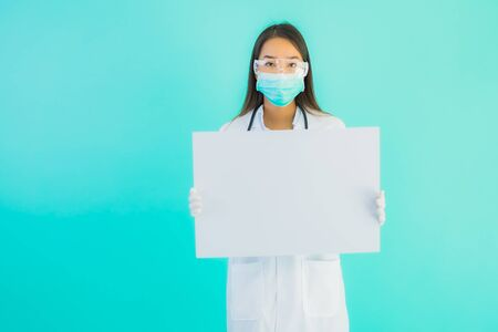 Portrait beautiful young asian doctor woman with empty card billboard banner on blue isolated background