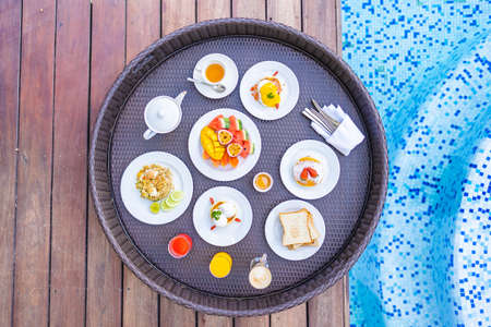 Flotaing breakfast tray around outdoor swimming pool with bread fruit egg coffee cup and juice 스톡 콘텐츠