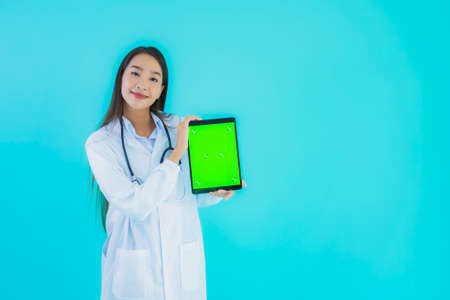 Portrait beautiful young asian doctor woman with stethoscope and smart tablet for use in hospital and clinic on blue isolated background Stock fotó
