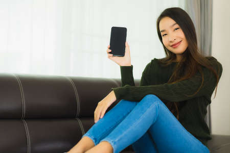 Portrait beautiful young asian woman use smart mobile phone or cellphone on sofa in living room interior Stock fotó