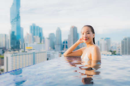 Portrait beautiful young asian woman relax happy smile leisure around outdoor swimming pool with cityscape