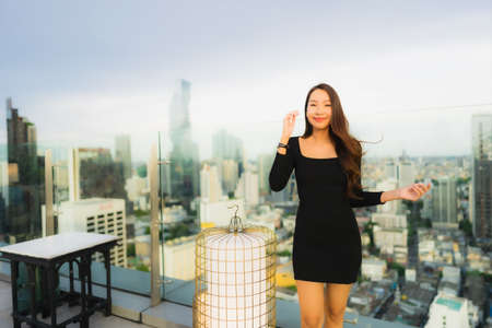 Portrait beautiful young asian woman at rooftop bar and restaurant around cityscape view