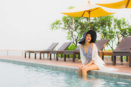 Portrait young asian woman happy smile relax around outdoor swimming pool in hotel resort for travel vacation 스톡 콘텐츠