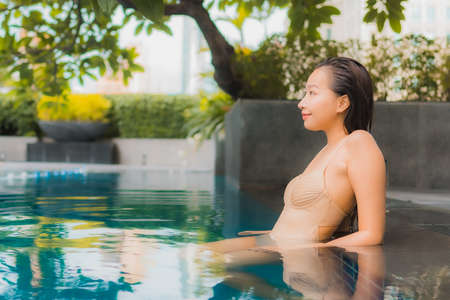 Portrait beautiful young asian woman relax happy smile leisure around outdoor swimming pool in resort