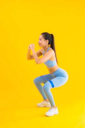Portrait beautiful young asian woman wear sportwear with sport rubber ready for exercise on yellow isolated background Imagens