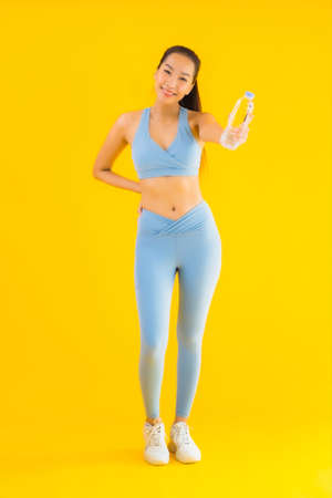 Portrait beautiful young asian woman with bottle water on yellow isolated background