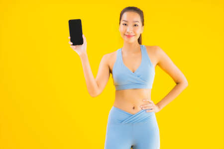 Portrait beautiful young asian woman wear sportwear with smart mobile phone on yellow isolated background 免版税图像