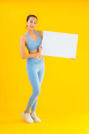 Portrait beautiful young asian woman wear sportwear show empty white billboard on yellow isolated background