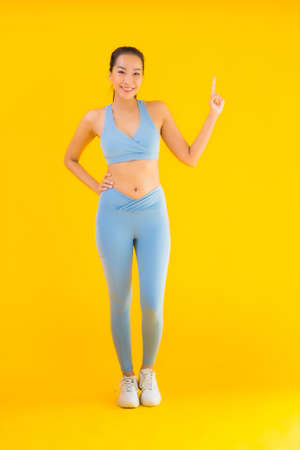 Portrait beautiful young asian sport woman with sportwear ready for exercise on yellow isolated background