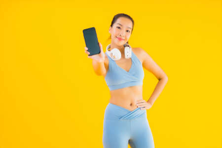 Portrait beautiful young asian woman wear sport wear with smart phone and headphone for listen music on yellow background 免版税图像