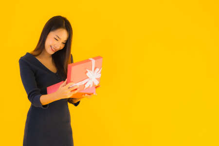 Portrait beautiful young asian woman with giftbox on yellow isolated background Reklamní fotografie