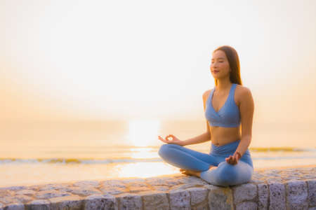 Portrait young asian woman do meditation around sea beach ocean at sunrise for health