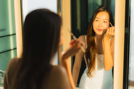 Portrait beautiful young asian woman make up with cosmetic powder and lipstick on her face facial in bathroom interior