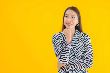 Portrait beautiful young asian woman smile happy with action on yellow isolated background