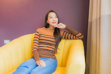 Portrait beautiful young asian woman relax smile in action on sofa in living room interior Фото со стока