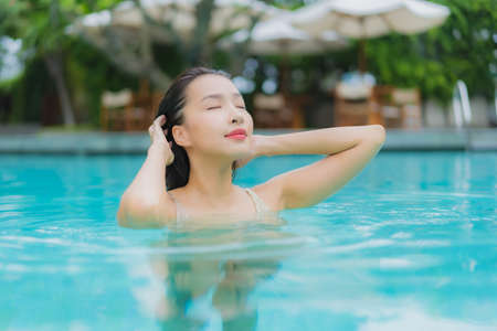 Portrait beautiful young asian woman relax smile around outdoor swimming pool in hotel resort for leisure vacation