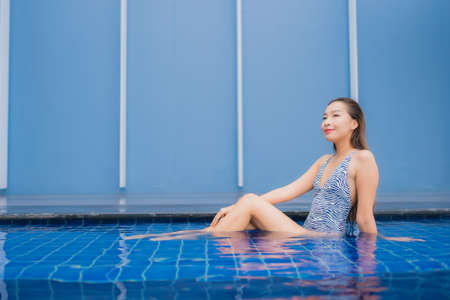 Portrait beautiful young asian woman relax smile around outdoor swimming pool for leisure vacation