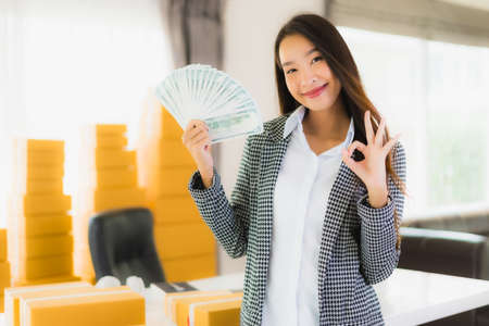 Portrait beautiful young asian woman work from home with laptop cash and cardboard box ready for shipping of online customer shopping