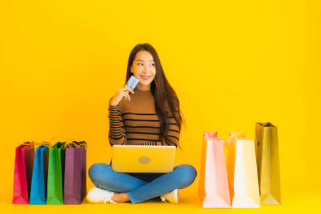 Beautiful portrait young asian woman sit on the floor with laptop or computer use credit card for online shopping around shopping bag on yellow background