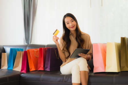 Portrait beautiful young asian woman online shopping with credit card and smartphone around shopping bag in living room