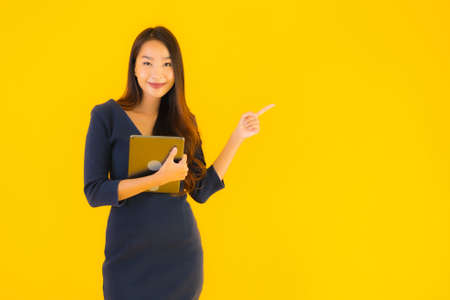 Portrait beautiful young asian woman with smart tablet electronic on yellow isolated background
