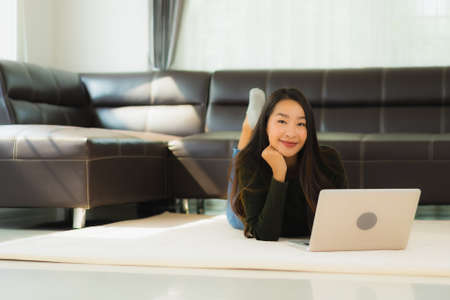 Portrait beautiful young asian woman use laptop computer with sofa in living room interior