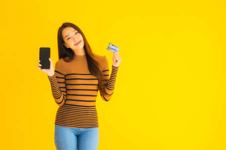 Portrait beautiful young asian woman use smart mobile phone or cellphone with credit card for online shopping on yellow isolated background