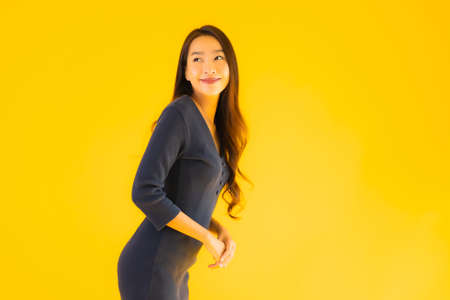 Portrait beautiful young asian woman with action on isolated yellow background